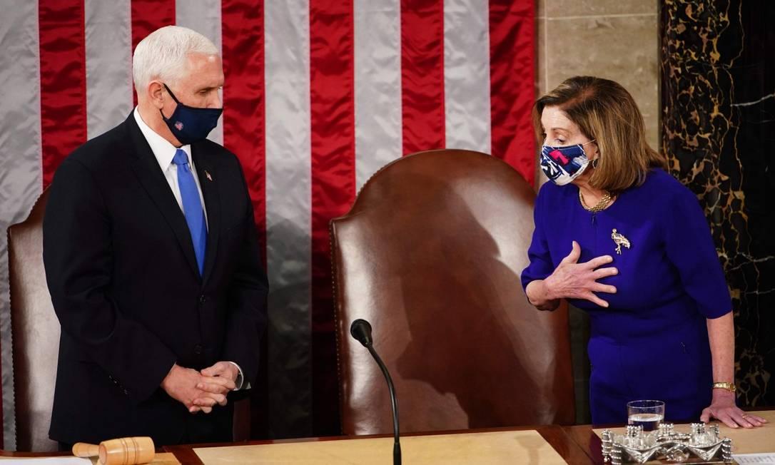 O vice-presidente dos Estados unidos, Mike Pence, e a presidente da Câmara, Nancy Pelosi, na sessão conjunta para oficializar a vitória de Joe Biden no Colégio Eleitoral Foto: JIM LO SCALZO / AFP