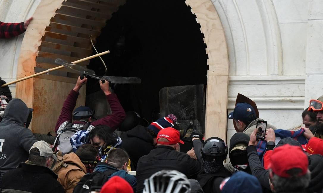 Apoiadores de Donald Trump arrombam a porta do Capitólio em Washington Foto: STEPHANIE KEITH / REUTERS