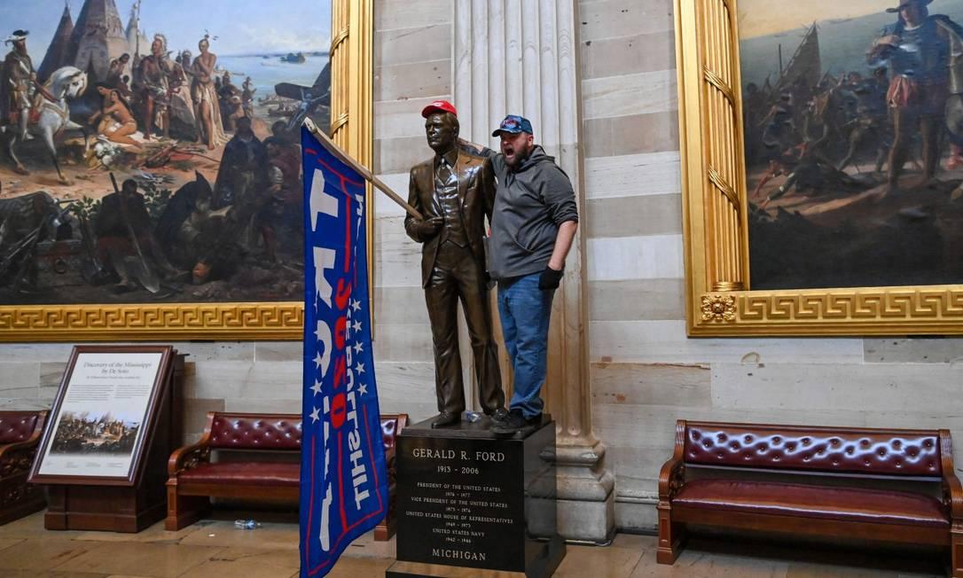 Apoiador de Donald Trump dentro da rotunda do Capitólio, ao lado da estátua de Gerald Ford, nesta quarta-feira Foto: SAUL LOEB / AFP