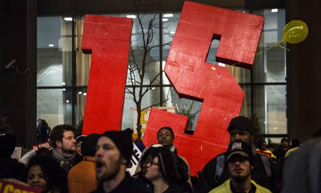 Manifestação a favor do aumento do salário-mínimo em frente a um hotel em Des Moines, Iowa: uma das primeiras promessas de Biden Foto: GABRIELLA DEMCZUK / NYT