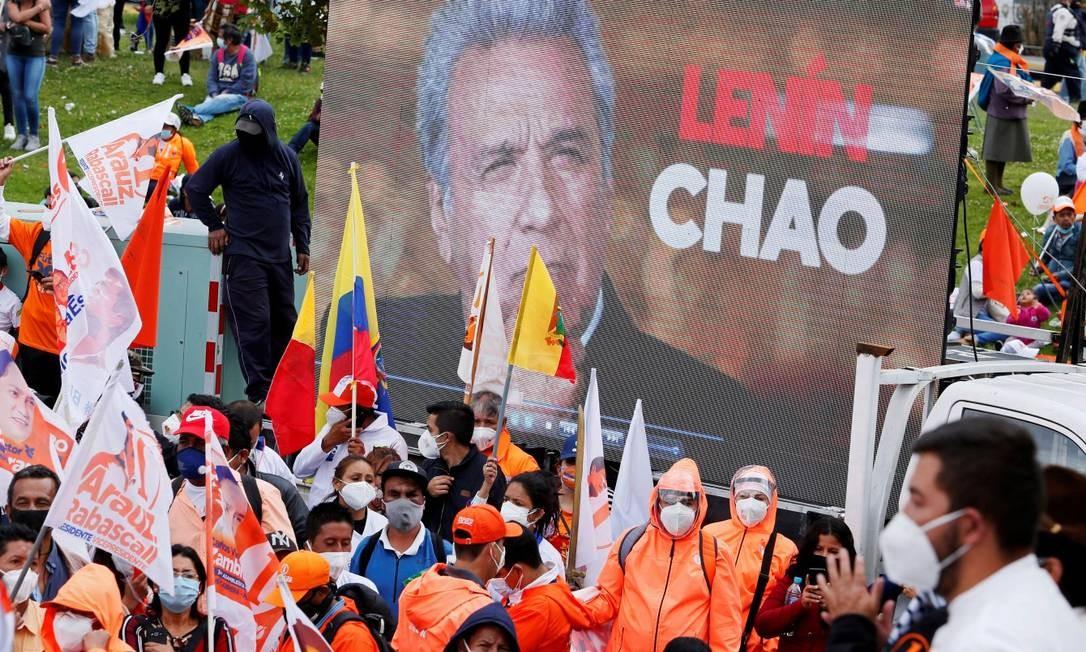 Apoiadores do candidato Andrpes Arauz no comício de encerramento da campanha, em frente a um cartaz onde se le