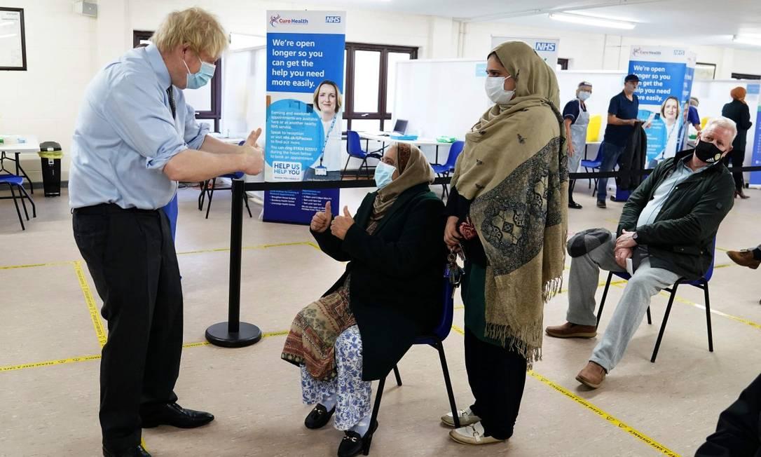 O primeiro-ministro do Reino Unido, Boris Johnson, gesticula para pessoas na fila para receber a vacina em Batley, Norte da Inglaterra, em 1º de fevereiro Foto: JON SUPER / AFP