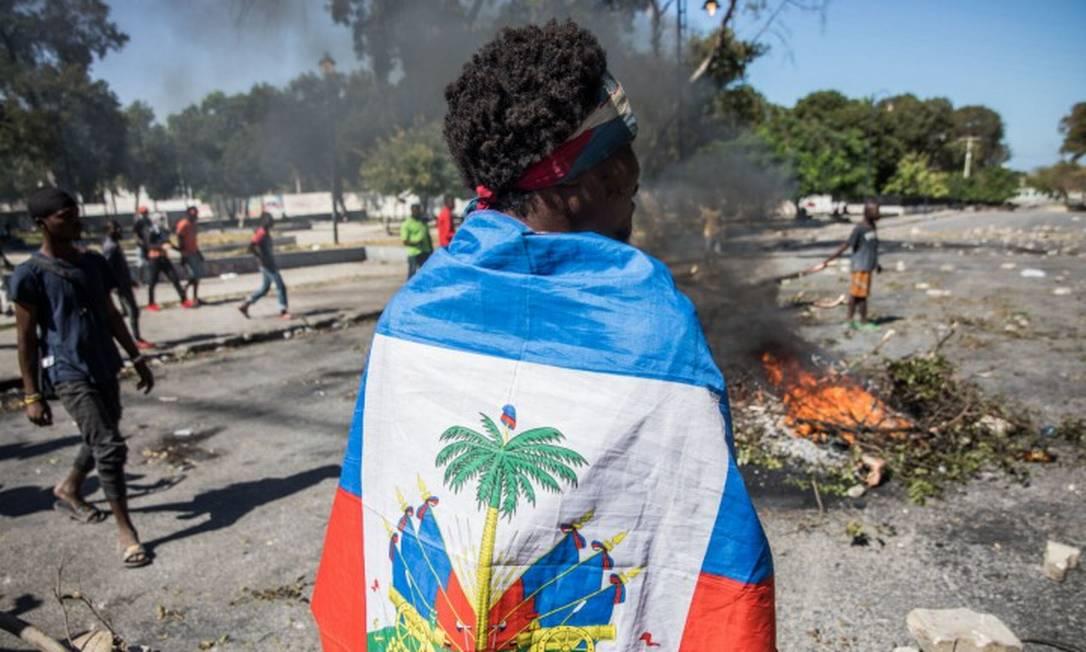 Manifestantes nas ruas de Porto Príncipe pedem a renúncia do presidente do Haiti neste domingo Foto: VALERIE BAERISWYL / AFP