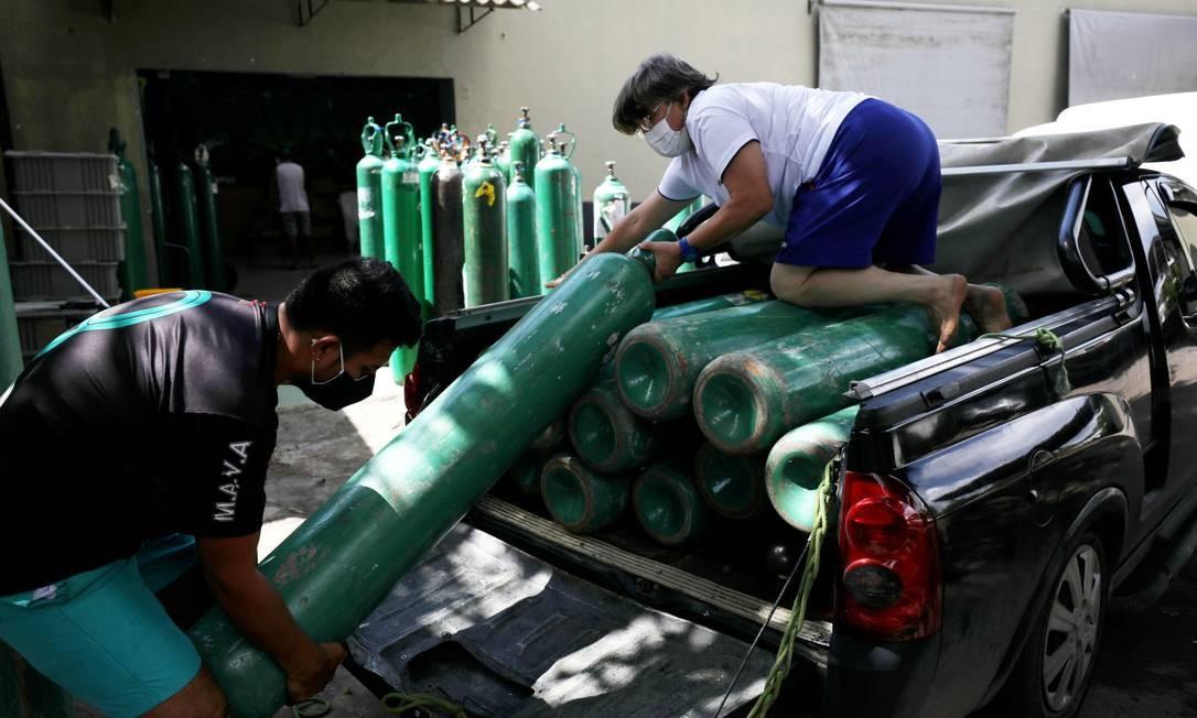 Pessoas retiram cilindros de oxigênio de picape em Manaus Foto: BRUNO KELLY / REUTERS