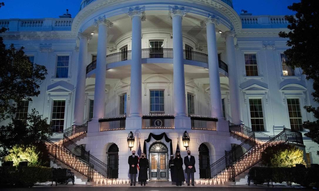 O presidente dos Estados Unidos, Joe Biden, a primeira-dama, Jill Biden, a vice-presidente, Kamala Harris, e seu marido, Doug Emhoff, fazem um minuto de silêncio em frente à Casa Branca repleta de velas Foto: SAUL LOEB / AFP