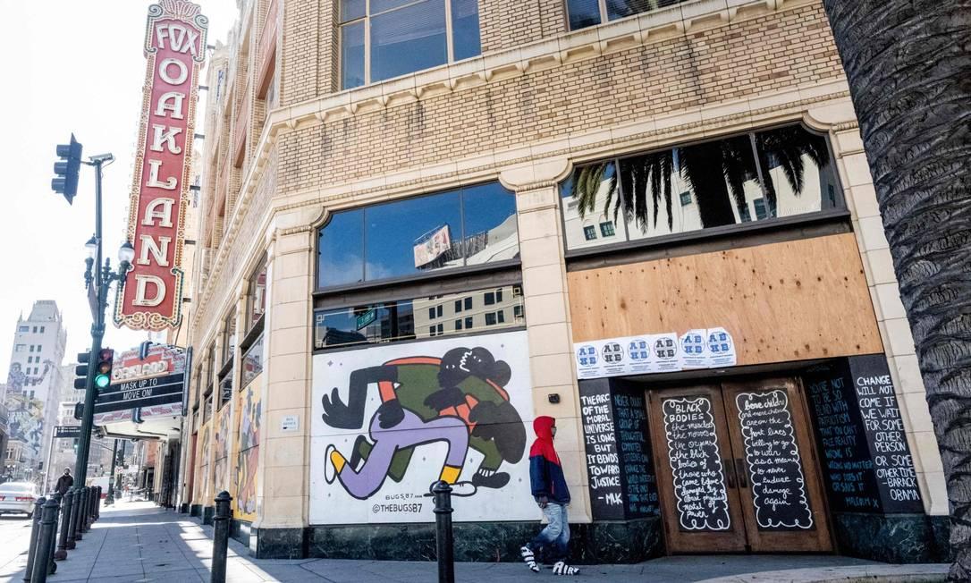 Homem caminha em frente a loja fechada em Oakland, na Califórnia Foto: JOSH EDELSON / AFP