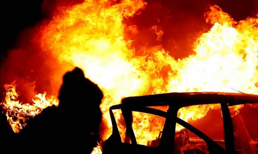 """Jovem revoltoso é visto perto de carro em chamas nos arredores do """"muro da paz"""" em noite de protestos em Belfast Foto: JASON CAIRNDUFF / REUTERS"""