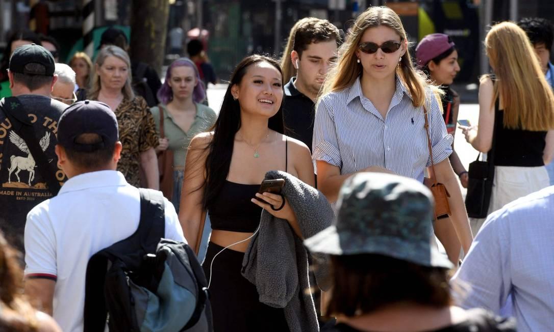 Pessoas caminham pelo distrito comercial de Melbourne, na Austrália, onde o vírus está controlado e não é preciso usar máscaras Foto: WILLIAM WEST / AFP