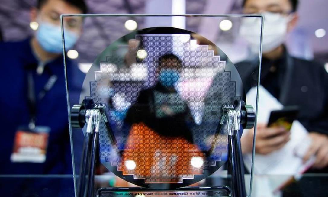 Visitantes observam a um dispositivo semicondutor exposto na Semicon China, uma feira de tecnologia de semicondutores, em Xangai, China, em 17 de março de 2021 Foto: Aly Song / Reuters