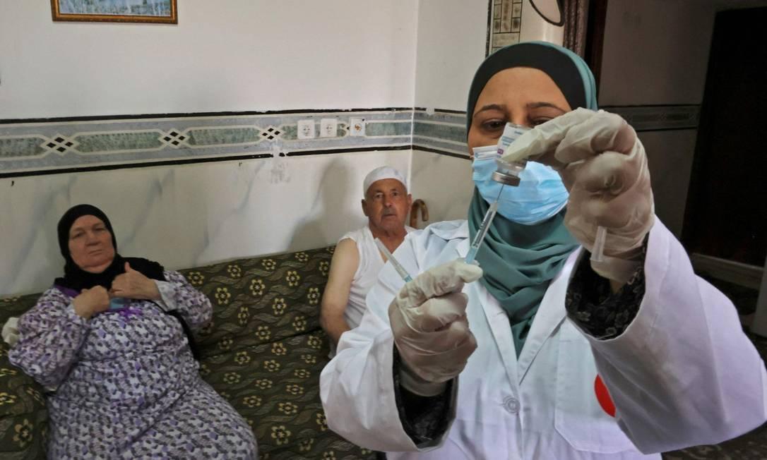 Uma profissional de saúde se prepara para vacinar uma família em Dura, perto de Hebron, na Cisjordânia ocupada Foto: HAZEM BADER / AFP 9-6-21