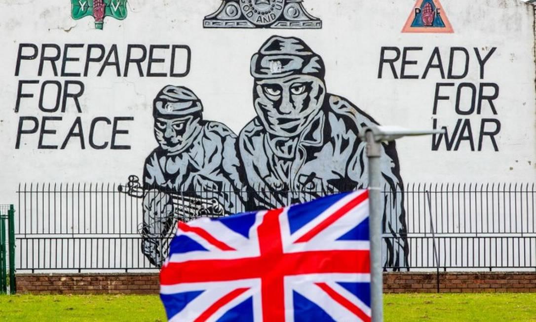 Uma bandeira britânica diante de um mural com voluntários norte-irlandeses em Belfast aponta para o mais grave problema causado pelo Brexit: a ameaça à estabilidade do reino Foto: Paul Faith / Bloomberg