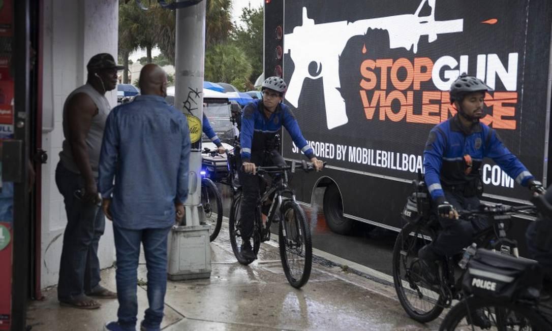 Policiais fazem patrulha de bicicleta enquanto pessoas organizam marcha pela paz e contra a violência armada em Miami Foto: JOE RAEDLE / AFP