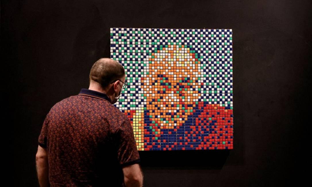 Homem em frente a um mosaico do Dalai Lama feito pelo artista urbano francês Invader, em uma exposição em junho de 2021 Foto: THOMAS SAMSON / AFP