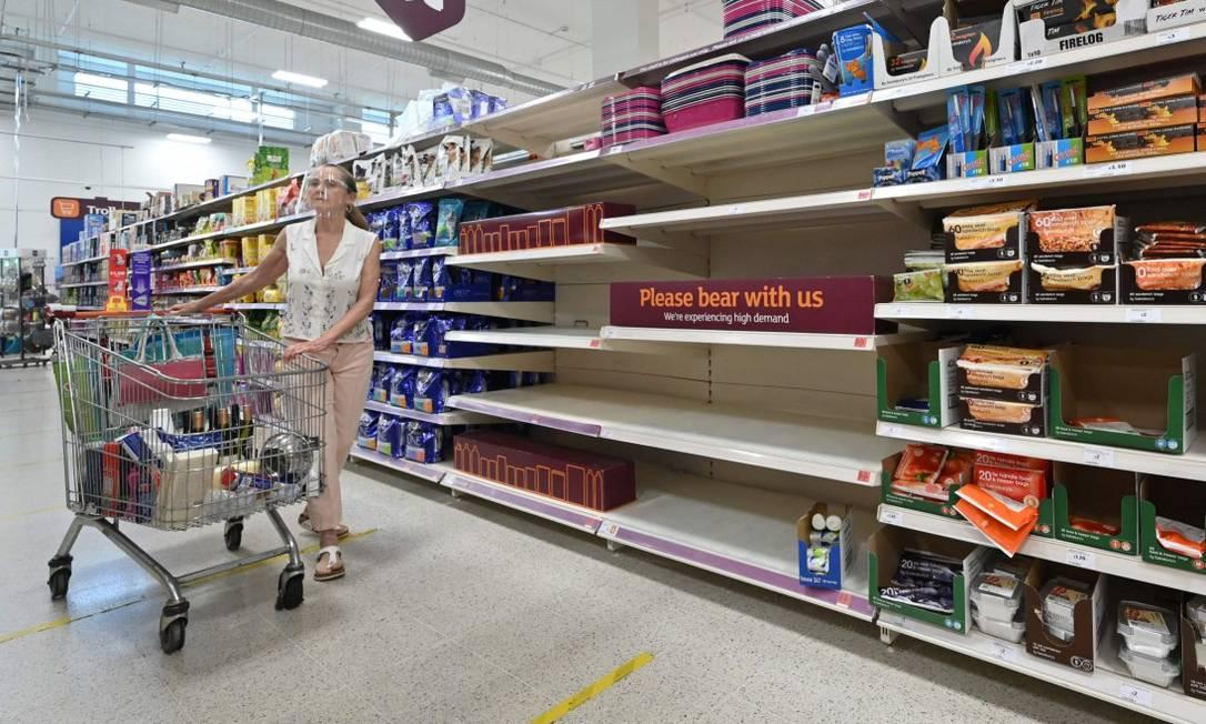 Consumidora em frente a aviso que produtos estão temporariamente indisponíveis em mercado em Nine Elms, no Sul de Londres Foto: JUSTIN TALLIS / AFP