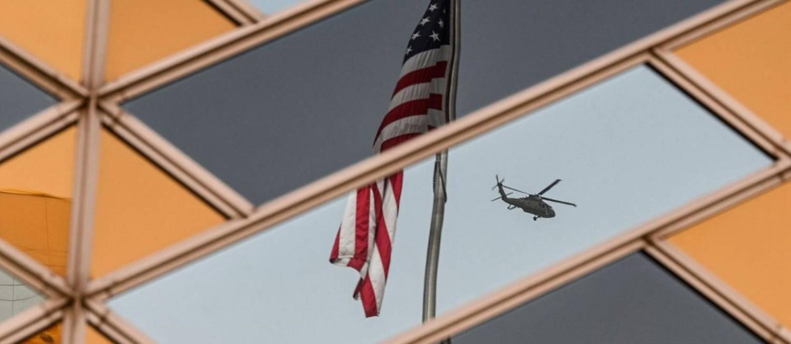 A bandeira dos Estados Unidos refletida na embaixada americana em Cabul com um helicóptero ao fundo Foto: SAJJAD HUSSAIN / AFP