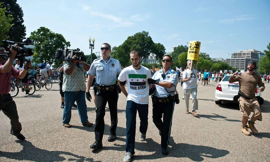 Manifestante sírio é preso após confusão durante protesto, em frente à Casa Branca, contra ação militar dos EUA ao país. O Congresso americano vai debater um possível ataque na semana do dia 9 de setembro Foto: NICHOLAS KAMM / AFP