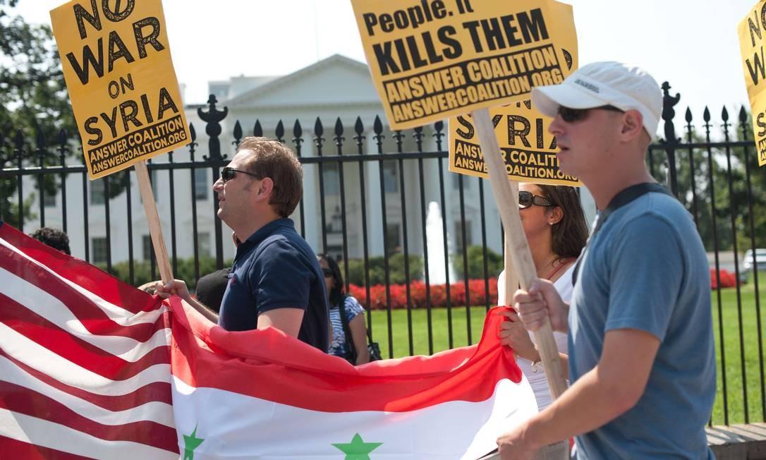 """""""Sem guerra na Síria"""". Manifestantes carregam cartazes, em frente à Casa Branca, em protesto contra intervenção militar americana na Síria Foto: NICHOLAS KAMM / AFP"""