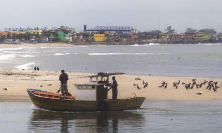 Pescadores entram na Barra do rio Macaé com a favela ao fundo: contraste comum no Norte Fluminense Foto: Antonio Scorza / Agência O Globo