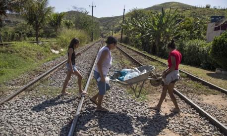 Clea e as filhas cruzam a linha do trem com água para beber Foto: Antonio Scorza / Agência O Globo