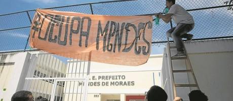 Alunos tentavam fixar faixa com símbolo da ocupação. No início do ano, eles dizem ter protestado pela instalação de ar-condicionado nas salas — e funcionou Foto: Márcia Foletto / Agência O Globo