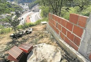 Construção é erguida perto de encosta sobre um dos túneis do BRT Transolímpico, em Jacarepaguá Foto: Gabriel de Paiva / Agência O Globo