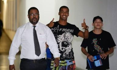 O jogador Lucas Perdomo (de boné) chega na delegacia para depor Foto: Pablo Jacob / Agência O Globo