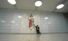 Funcionário limpa o painel da artista plástica Marina Lloyd na Estação Nossa Senhora da Paz, em Ipanema. A obra é feita de azulejos, vidro e pedras Foto: Márcia Folleto / Agência O Globo