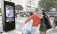 Em totens da Orla de Copacabana, cariocas e turistas fazem fotos e pesquisam informações sobre o transporte público: indicações também têm problemas