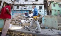Michael Bates passa ao lado de uma favela na Avenida Martin Luther King: 300 dias andando. pela Trégua Olímpica Foto: Alexandre Cassiano / Agência O Globo
