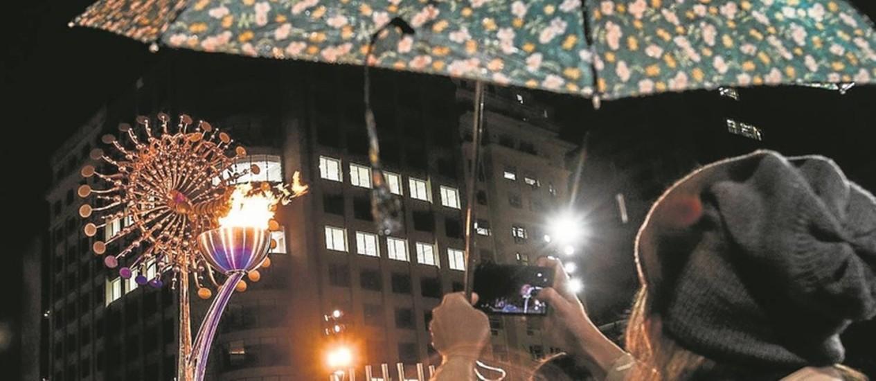 Curiosos fazem fotos diante da pira olímpica instalada no Centro: com a frente fria, o lugar ficou menos concorrido Foto: Bárbara Lopes / Agência O Globo