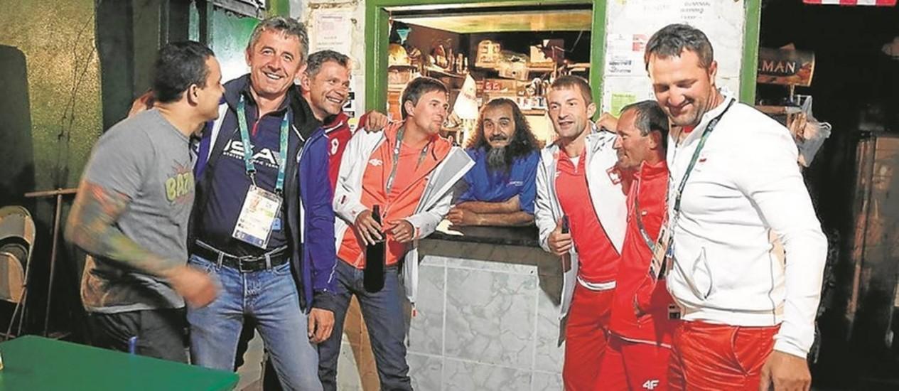 José Felipe de Araújo, o Bin Laden, junto a integrantes de delegações estrangeiras em seu bar Foto: Fabio Rossi / Agência O Globo