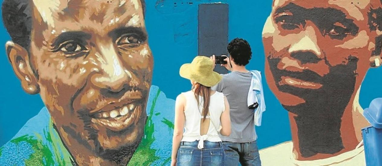 Turistas observam as imagens dos corredores Yonas Kinde e Anjelina Nada Lohalith, do time de refugiados Foto: Paulo Nicolella