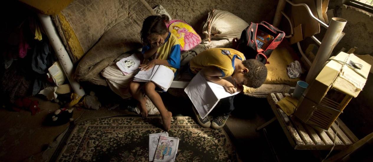 Crianças estudam em uma casa erguida na beira de um rio em Belford Roxo: imagem foi vencedora na categoria Reportagem Fotográfica Foto: Márca Foletto / Agência O Globo