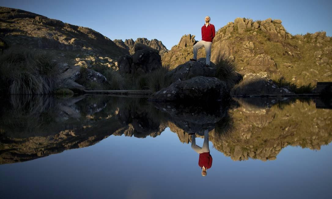 O frequentador do Parque Nacional do Itatiaia Germano Viegas observa a represa do Abrigo Rebouças com as Agulhas Negras ao fundo, no centro. Mesmo em dias ensolarados e sem nuvens, o frio impera do outono Foto: Márcia Foletto / Agência O Globo