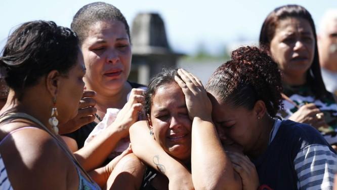 Parentes de Marcelo da Silva Vaz, morto durante operação no Complexo do Salgueiro, em São Gonçalo, se abraçam e choram durante sepultamento do rapaz Foto: Pablo Jacob / Agência O Globo