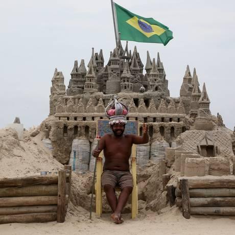 O escultor Márcio Mizael Matolas, de 44 anos, na porta de casa, o castelo de areia na Praia do Pepê onde mora Foto: Custódio Coimbra / Agência O Globo
