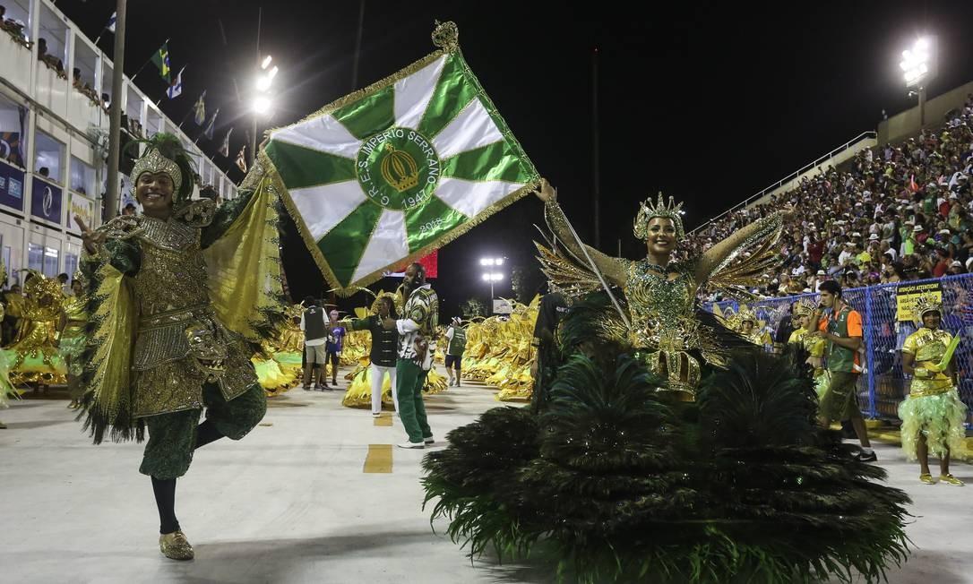 Mestre-sala e porta-bandeira do Império Serrano exibem a bandeira da escola pelo Sambódromo Foto: Fabiano Rocha / Agência O Globo