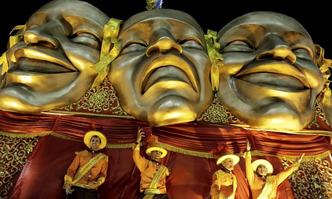 Em alegoria, componentes da Unidos da Tijuca se misturam ao dourado das máscaras de teatro Guito Moreto / Agência O Globo