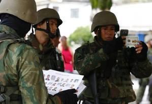 Militar do Exército fotografa morador, enquanto outro confere lista de suspeitos da Operação Ficha Limpa Foto: Pablo Jacob / Agência O Globo
