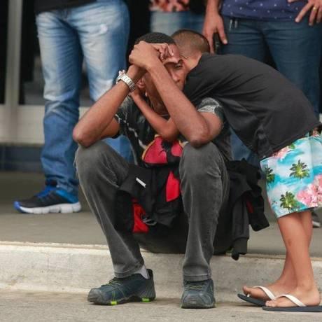 O marido de Vânia, Carlos Alberto Lopes, é consolado pelo sobrinho em frente ao Hospital municipal Moacyr do Carmo, em Duque de Caxias Foto: Brenno Carvalho / Agência O Globo