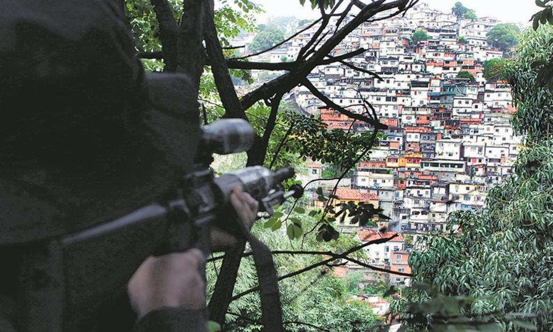 Um sniper da PM mira em direção a uma favela de Santa Teresa: governador eleito defende que agentes atirem em bandidos que estejam portando fuzis, mas juristas dizem que proposta fere a Constituição e o Código Penal Foto: Cléber Júnior