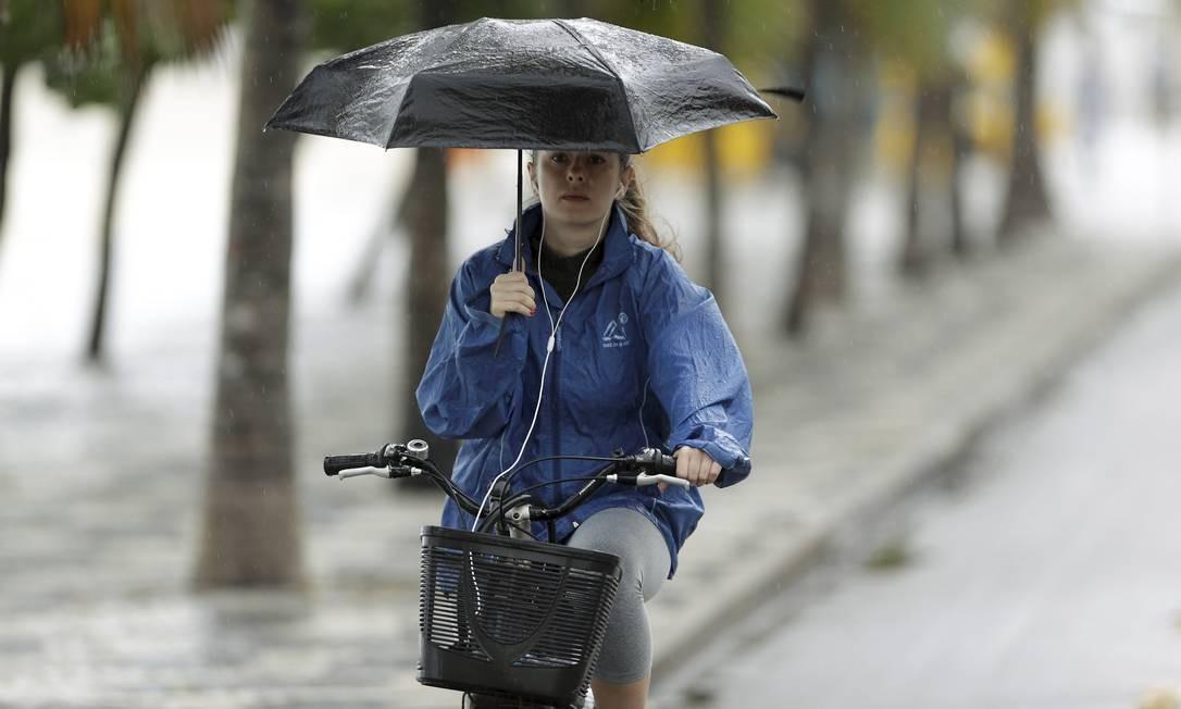 De guarda-chuva, ciclista circular pela orla da Zona Sul do Rio Foto: Gabriel de Paiva / Agência O Globo