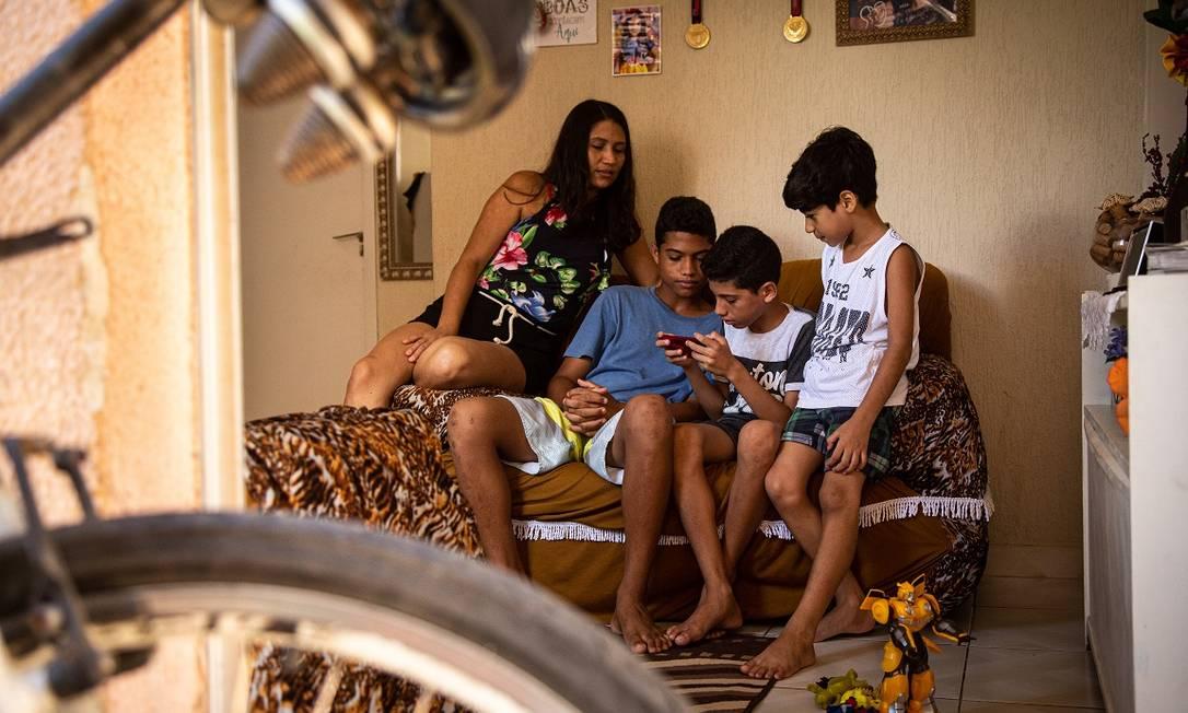 Juciane tenta trabalhar enquanto os filhos disputam o único celular da família Foto: Hermes de Paula / Agência O Globo