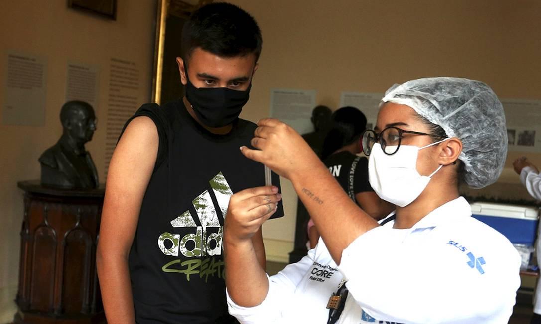 Adolescente observa profissional de saúde preparar a vacina no posto do Palácio do Catete Foto: Fabiano Rocha / Agência O Globo