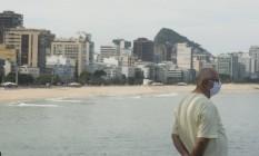 Idoso usando mascara observa a praia do Leblon desde o Mirante Foto: Antonio Scorza / Agência O Globo