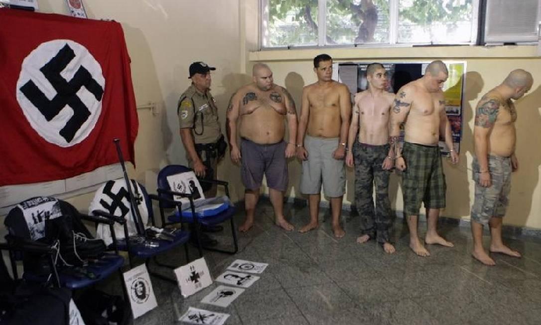 Neonazistas. O grupo detido na delegacia ao lado do material com a suástica Foto: Luiz Ackermann / Extra / Agência O Globo
