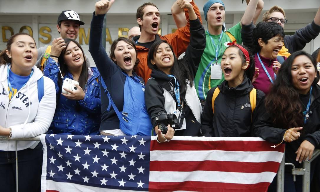 Jovens gritam atrás da bandeira dos Estados Unidos, em Copacabana Foto: Daniela Dacorso / Agência O Globo
