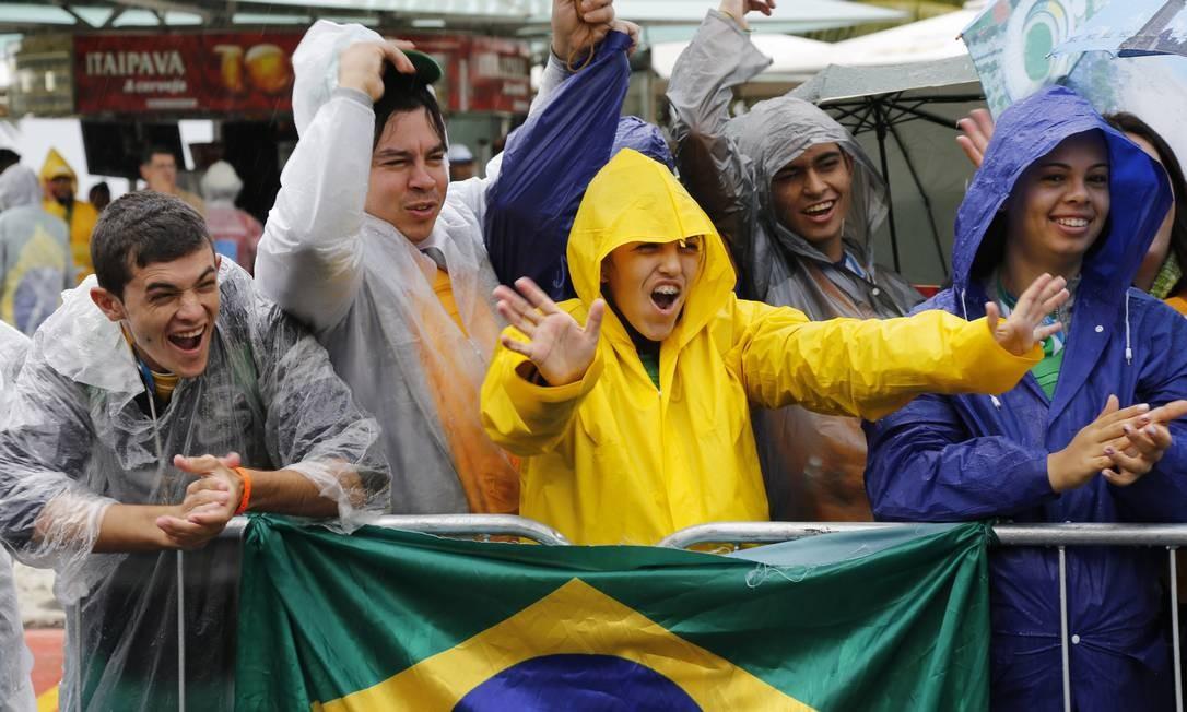 Grupo de brasileiros mostra animação mesmo sob a chuva que atinge o bairro Mônica Imbuzeiro / Agência O Globo