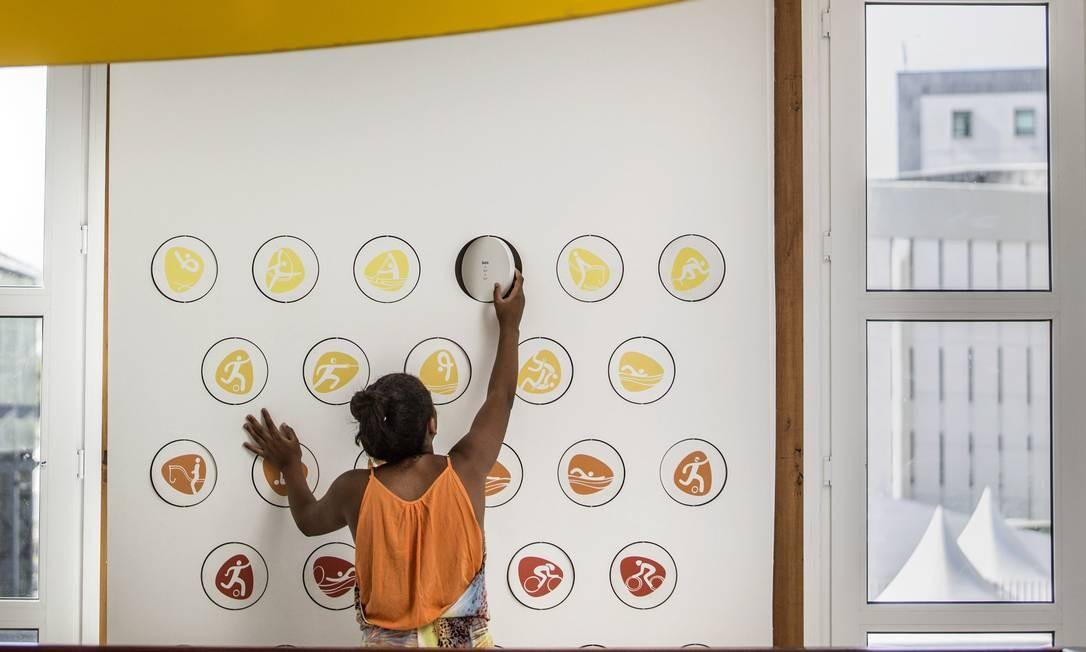 Jovem brinca na parede onde há descrições sobre os esportes Foto: Ana Branco / Agência O Globo
