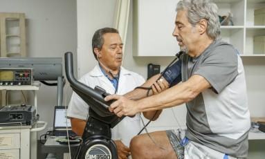 O médico José Antônio Calda monitora Sérgio Bogado enquanto ele faz exercícios Foto: Analice Paron / Agência O Globo